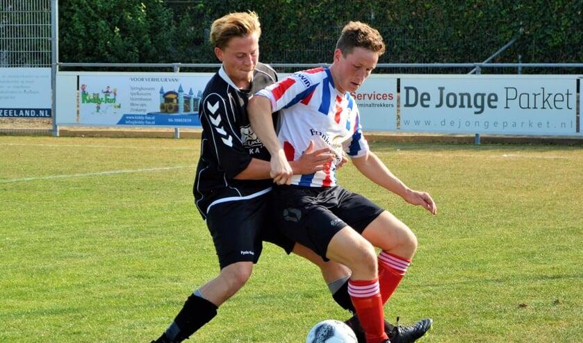 Bastiaan van Dijk (Krabbendijke) in duel met Ries de Jonge (Kapelle) in de gemeente-derby.