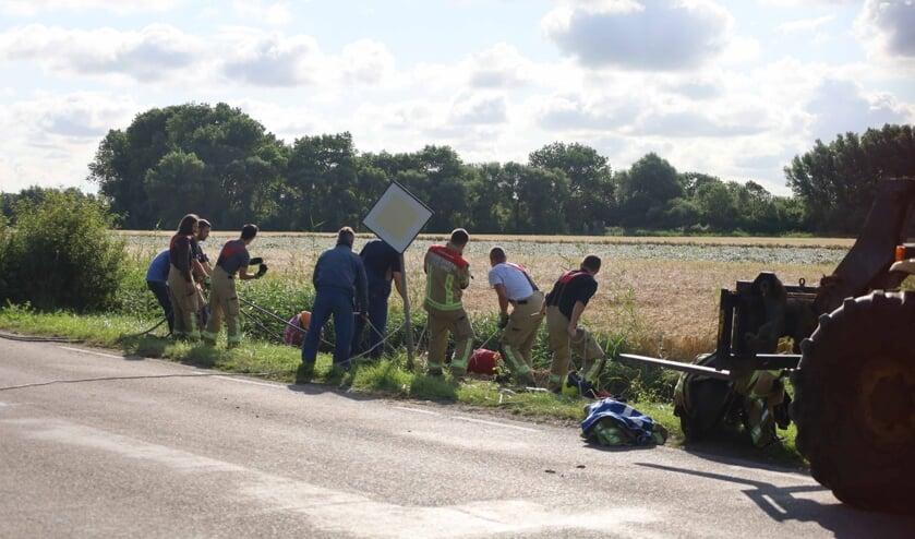 Hulpverleners doen een poging het paard uit de sloot te trekken langs de Prelaatweg
