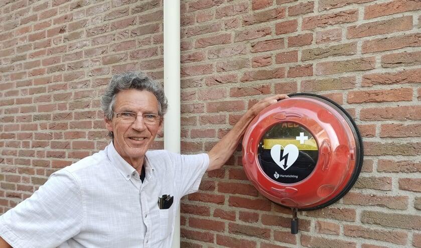 <p>John Schuurmans bij de AED aan zijn huis.</p>
