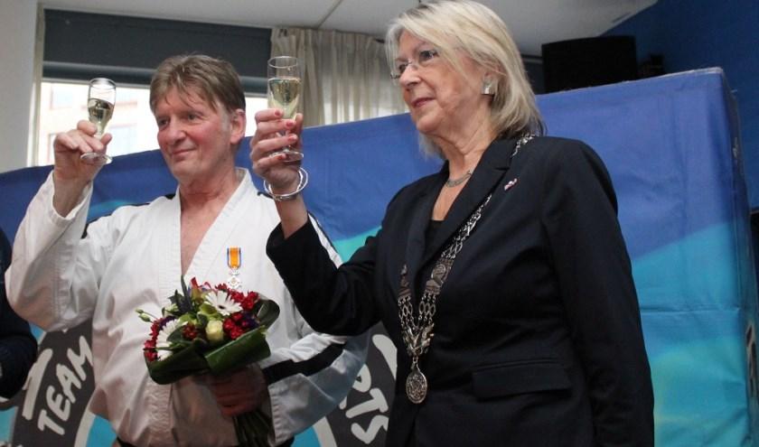 Jan Koster heft het glas met burgemeester Francisca Ravestein van Pijnacker die hem zojuist een Koninklijke onderscheiding heeft opgespeld (foto: Jan Wenteler)