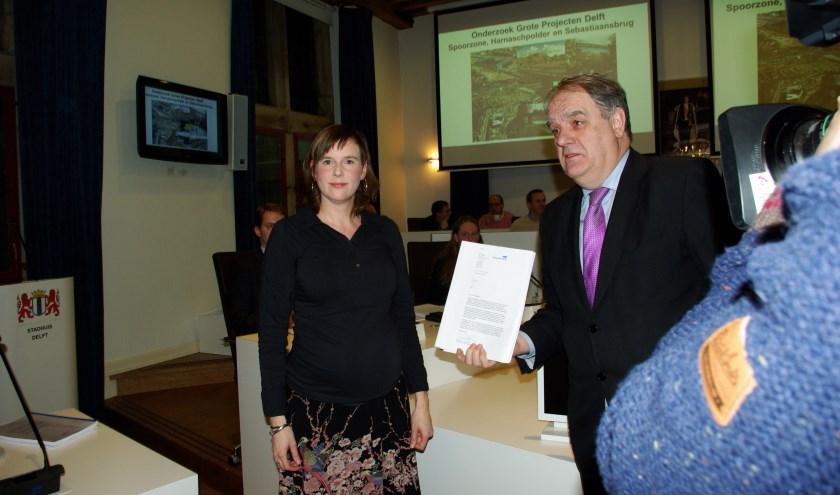 Burgemeester Bas Verkerk (rechts) ontving het eerste exemplaar van het onderzoek naar de financiële malaise waarin Delft verzeild is geraakt. Links Lieke van Rossum, voorzitter van de onderzoekscommissie.