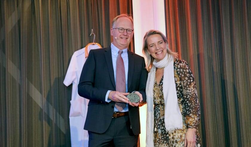 Kinderarts Nico van der Lely met de penning, overhandigd door directeur Carina Hilders