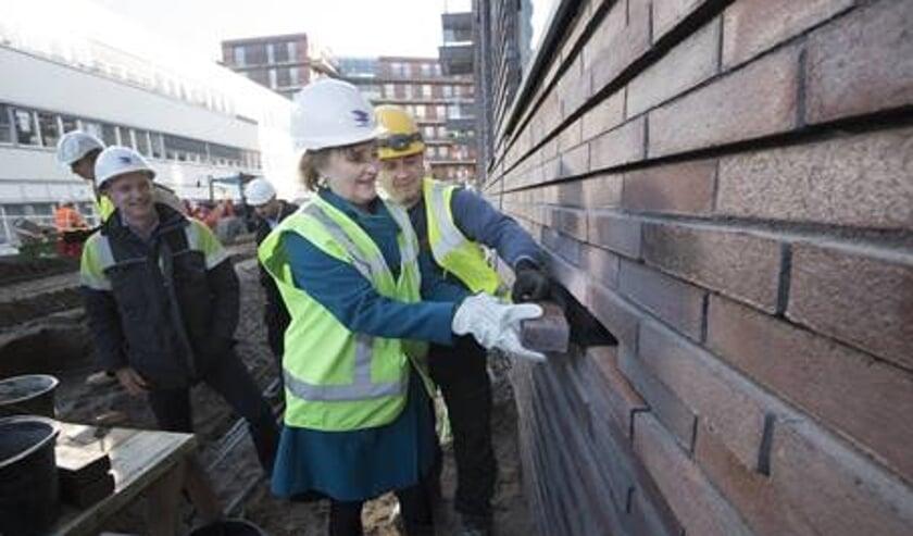Wethouder Martina Huijsmans metselt de laatste steen in de buitenkant van het woningproject VOLT in.