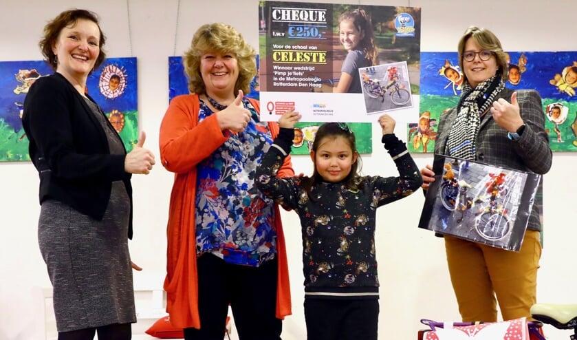 Celeste showt met trots de door haar gewonnen cheque. Links staat wethouder Huijsmans