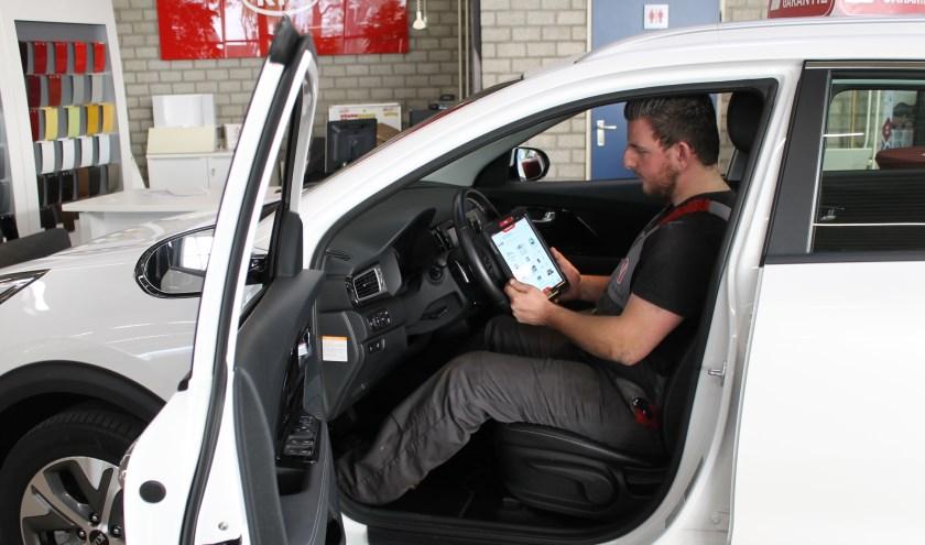 Medewerker Sjoerd Wijsman in de werkplaats bezig met het uitlezen van eventuele storingen in de auto-elektronica.