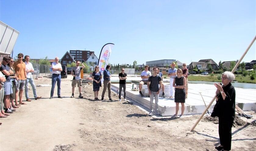 Wethouder Karin Schrederhof (rechts) verricht samen met de toekomstige bewoners de starthandeling.