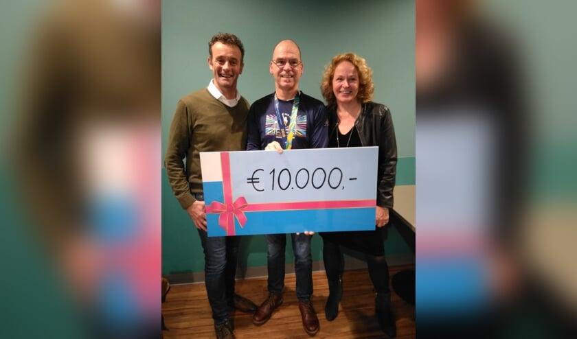 Nico Heijker overhandigd zijn donatie aan  Peter Ausems en Irma van Gelderen