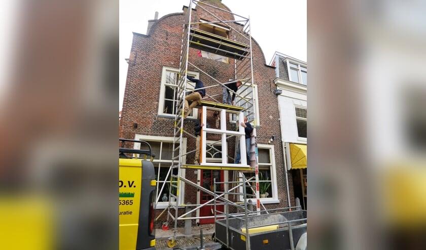 <p>Gebroeders Mensert aan het werk op de steiger in de Delftse binnenstad.</p>