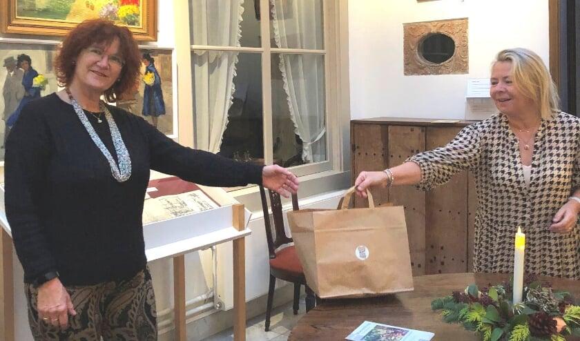 Carin Kraal – van der Leeuw (rechts) overhandigt de kerstgoodiebag aan vrijwilligster Rieneke de Pater in Museum Paul Tetar van Elven