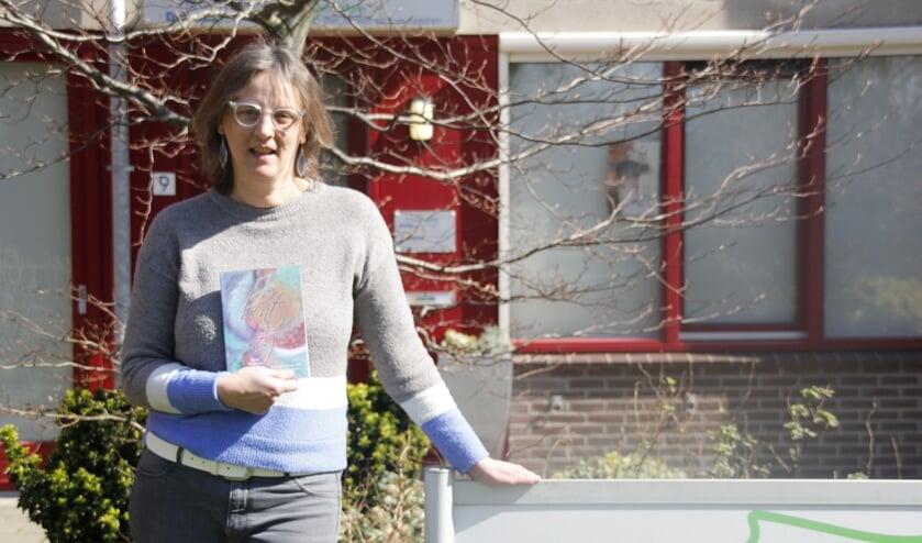 Anja Buurman (54), in haar hand haar gedichtenbundel 'Je bent er nog'.