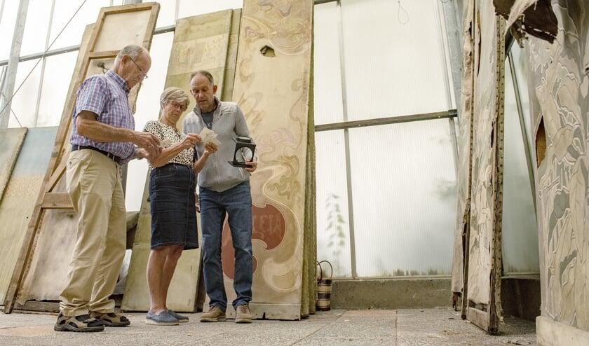 Aad en Toni van der Meer samen met Marcel van Dien druk bezig om aan de hand van foto's de juiste volgorde van de panelen te bepalen (Foto: Roel van Dorsten)