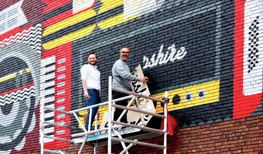 <p>Wethouder Bas Vollebregt en kunstenaar Micha de Bie leggen de laatste hand aan het kunstwerk (Foto: Koos Bommel&eacute;)</p>
