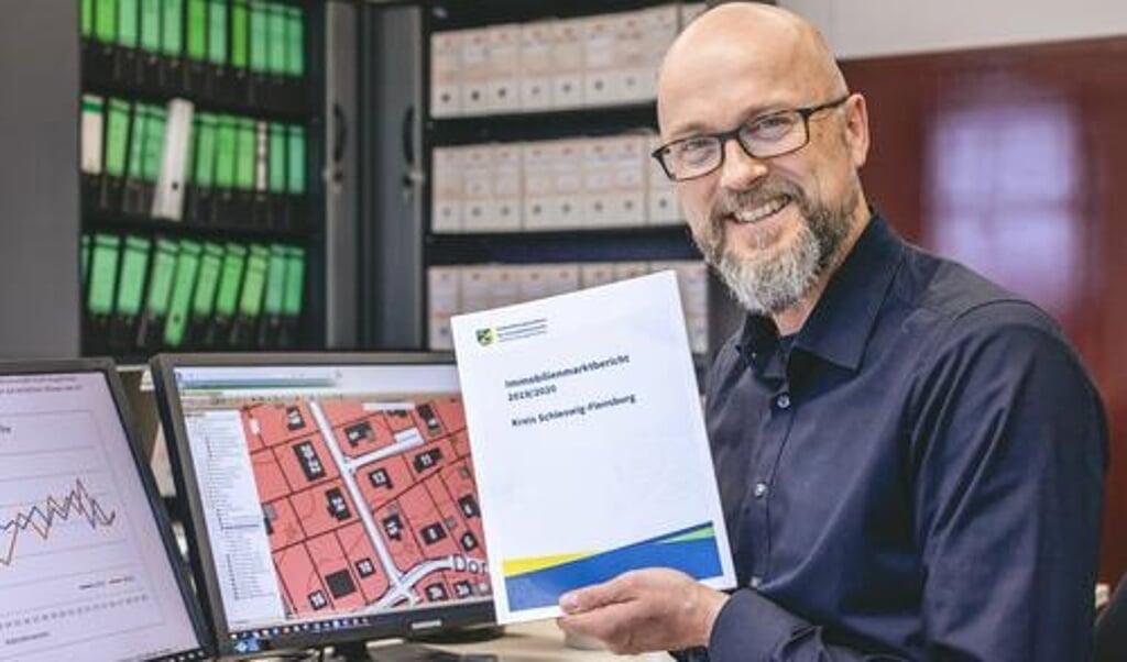 <p>Jasper Thiesen, Vorsitzender des Gutachterausschusses, h&auml;lt den neuen Immobilienmarktbericht in der Hand.</p>  (Kreis Schleswig-Flensburg)