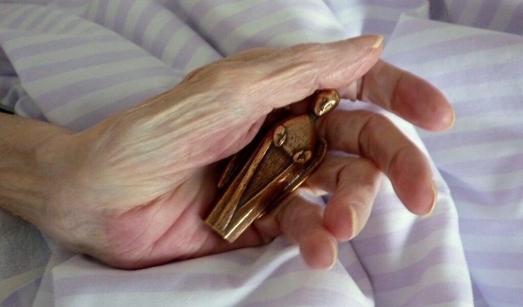 Bronzeenglen ligger godt og tungt i hånden. Den er modsat et krucifiks ikke nødvendigvis forbundet med kristendommen. Som Kirsten Bühler siger, så mennesker i tusindvis af år brugt engle som symboler.  ( Sankt Lucas Hospice)