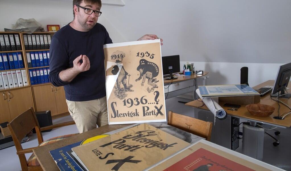 Museumsleder Hauke Grella med et udvalg af Slesvigsk Partis valgplakater, som indgår i udstillingen.  (Ruth Maria Candussi)