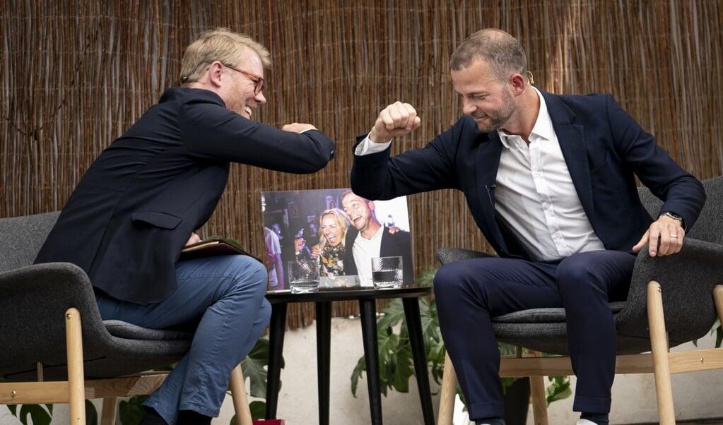 """Det nye opslagsord """"albuehilsen"""" har to betydninger ifølge Dansk Sprognævn. Den nyeste betydning kan dateres til 2020 og er den hilsen, vi under coronapandemien foretager med albuen i stedet for håndtryk eller knus.Den ældste betydning af ordet er derimod kendt fra fodboldverdenen og er et """"stød med albuen mod en modspiller"""". Her var det fhv. partileder Morten Østergaard (RV) og journalist Søren Lippert, der gav en albuehilsen i sommer.  ( Niels Christian Vilmann/Ritzau Scanpix)"""