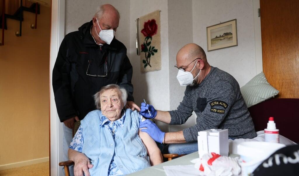 Også på øerne og halligerne er vaccinationerne mod corona nu gået i gang. Her vaccinerer ældreplejer Thomas Hedderich (t.h.) den 92-årige Anke Diedrichsen (92) fra Hallig Hooge. Læge Gerhard Steinort holder øje.   (Christian Charius, dpa)