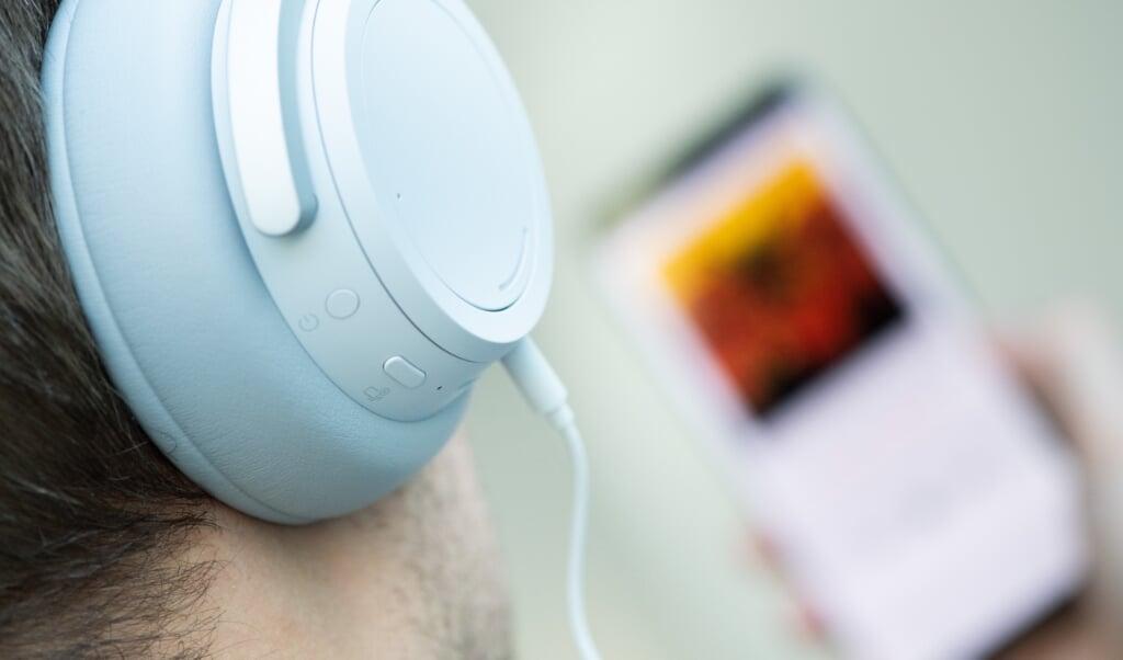 Ein Mann hört mit Kopfhörern Musik von seinem Smartphone. Dank großer Zuwächse im Audio-Streaming hat die deutsche Musikindustrie die Folgen der Corona-Pandemie beim Umsatz 2020 gut weggesteckt.   (Franziska Gabbert, dpa)