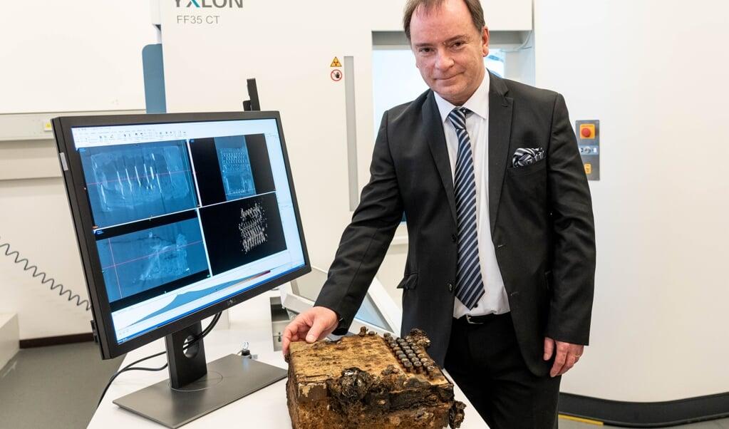 Thorsten Buzug, geschäftsführender Direktor der Fraunhofer-Einrichtung für individualisierte und zellbasierte Medizintechnik (IMTE), zeigt eine Enigma-Verschlüsselungsmaschine, die mit einem Computertomographen aus der Medizintechnik untersucht wurde.    (Axel Heimken, dpa)