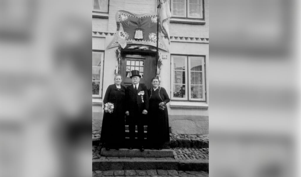 Billederne viser Julius C. E. Hansen julen 1928 og til sin 100-års fødselsdag med sin tredje kone og datteren Anna foran huset i Kalvegade, der er pyntet med husarregimentets flag.  (Privat)