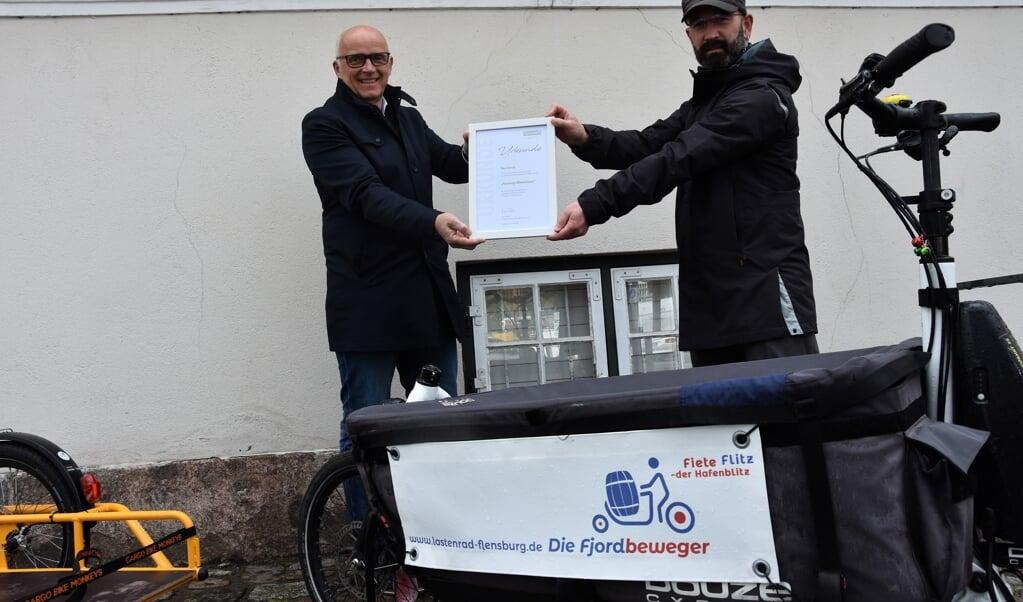 Timo Schmidt (re.) wurde für seinen Einsatz bei den Fjordbewegern von Klimapakt-Vorsitzenden Jürgen Möller ausgezeichnet.  ( Klimapakt Flensburg)