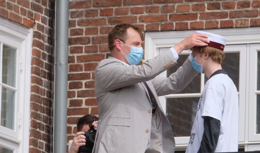 I år gav rektor Heino Aggerdam personligt studenterne hue på. En ny tradition er dog skabt, da eleverne modtog huen på skolens balkon.  ( Sebastian Iwersen                                                                                                                                                                                                                                                     )