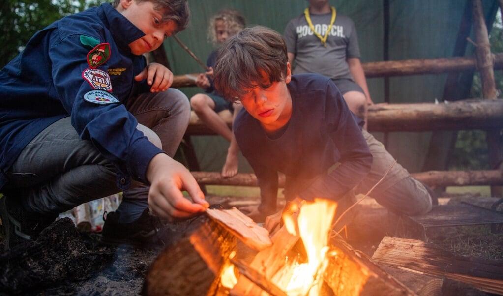 Fra venstre er det Ville og Vegar Vieland fra Angelbo spejderne i Husby, der tænder bålet til aftensmaden. Alt mad bliver lavet over bål og spist ved det hjemmelavede køkkenbord.    (Kira Kutscher)