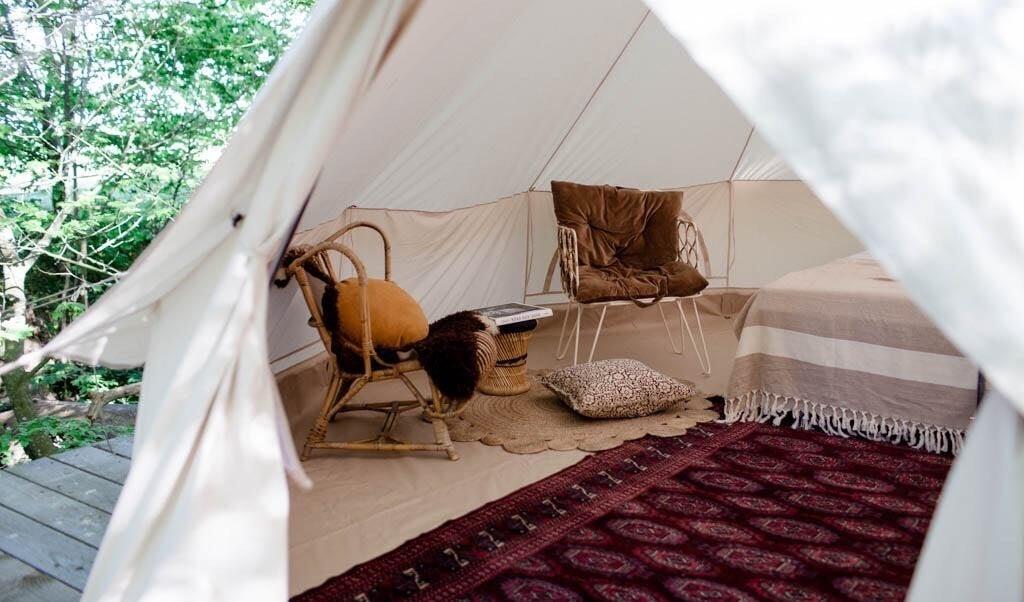 Det ægte tæppe på gulvet og den lune stemning leder tankerne lidt over mod safari, når man kigger ind i skovteltet. Dette befinder sig på Bornholm på Rø Jordbrug.   ( GoGlamping)