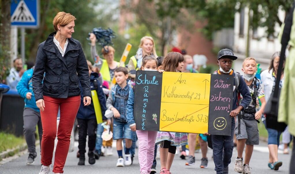 Med et skilt viste eleverne, hvor de var på vej hen, da de fik lov at gå på vejen hen mod den nye skole.   (Kira Kutscher)