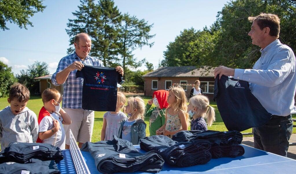 Hatlund-Langballe Danske Skole bliver tit glemt, når Stenbjergkirke Kommune giver noget til skoler, mener Jürgen Schiewer (t.h.), der med hjælp fra skoleleder Klaus Andersen onsdag delte t-shirts ud til hele skolen.  ( Kira Kutscher)