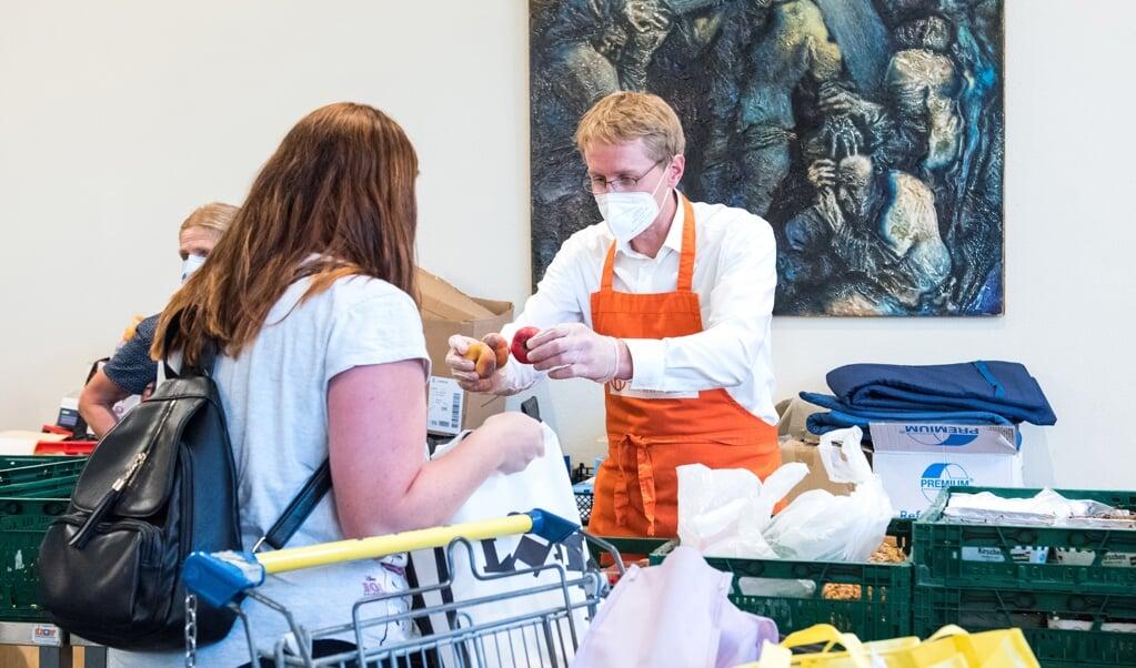 Ministerpräsident Daniel Günther packte während seiner Sommerreise auch bei der Husumer Tafel bei der Ausgabe von Lebensmitteln mit an.   (dpa)