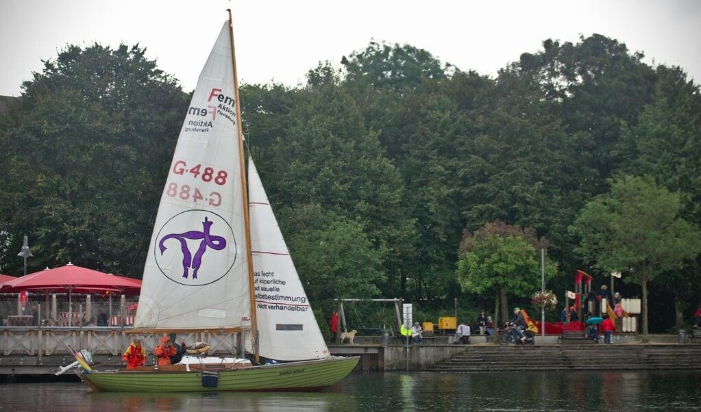 Med en lilla livmoder på sejlet lægger demonstrationsbåden »beeden scheef« til ved havnespidsen.   (Hanna Poddig)