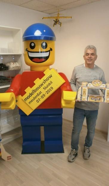 Organisator van de modelshow Johnny Bergakker bij een reuze pop van Lego.