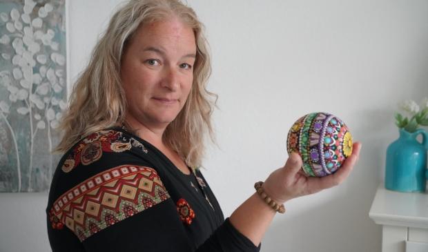 <p>Sylvia met een houten bol, die fraai met Dot painting is bewerkt.</p>