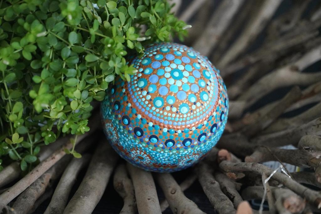 <p>Met Dot painting bewerkte houten bol.</p> Foto: Alex De Vliegere © hbnieuws