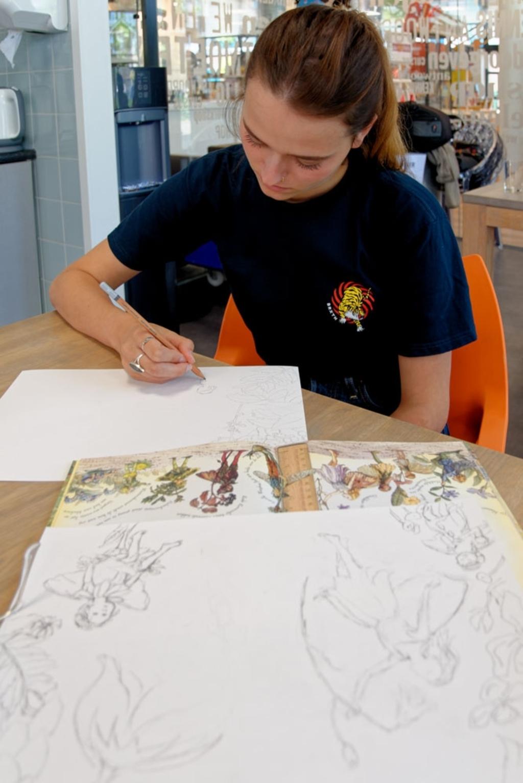 Laurie is bezig met een illustratie van elfjes in bloemen Lex Heijtveldt © hbnieuws