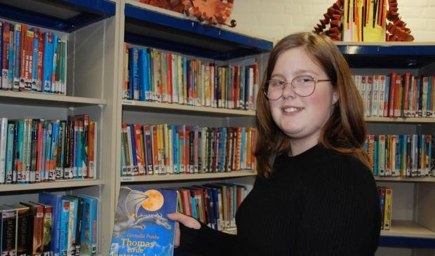 <p>Mara met haar favoriete boek in de bieb van Olympia</p>