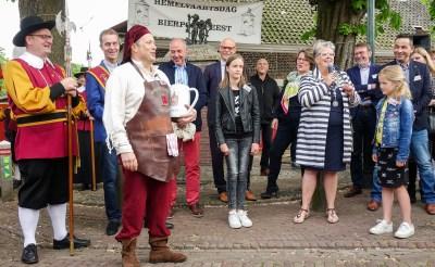 Burgemeester Jeannette Zwijnenburg verwelkomt de nieuwe Esschenaren met warme woorden, terwijl gemeentelijk dorpstapper Gerrie van der Mee klaarstaat met bierpullen. (Foto: Albert Stolwijk).