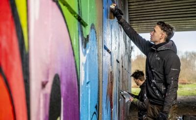 <p>Jan Pennings (op de voorgrond) van stichting Tunnel Vision Boxtel maakten in opdracht van het team van &lsquo;Boxtel &ndash; 2020 in 366 verhalen&rsquo; een graffitikunstwerk. Het fraaie resultaat is te zien in de verhalenbundel die begin 2021 verschijnt. (Foto: Peter de Koning).</p>