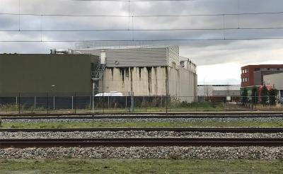 De natte plekken aan de buitenkant van het waterzuiveringsbassin van HydroBusinnes zijn duidelijk zichtbaar. De foto is genomen vanaf de Parallelweg Zuid, aan de overkant van het spoor. (Foto: PvdA-GroenLinks).