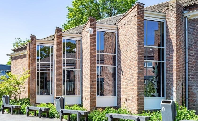 Tijdens de lezing in MuBo geeft architect Harrie van Helmond een fotorondleiding door het Jacob-Roelandslyceum. (Foto: Rini van Oirschot).