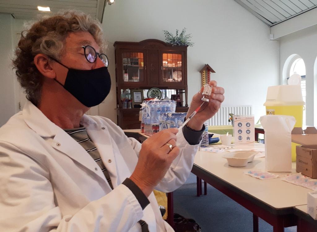 <p>Praktijkondersteuner Paul Handgraaf van gezondheidscentrum De Vier Kwartieren vult injectiespuiten met het AstraZeneca-vaccin tegen Covid-19. In elke ampul zit 5 milliliter waarmee maximaal elf vaccinaties toegediend kunnen worden. (Foto: Marc Cleutjens).</p>