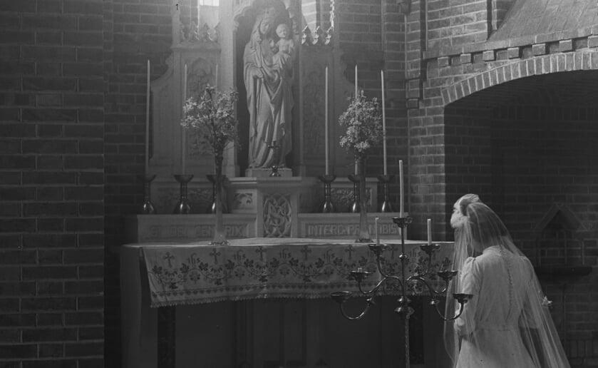 Een bruid knielt voor het Gemondse Maria-altaar. (Foto: BHIC)