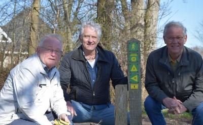 <p>Secretaris Jan Spijkers (links) en voorzitter Richard Permentier (rechts) van WSV De Keistampers plaatsten maandag met Henny van den Boom van stichting BELL het gele wegwijzerbordje van de 4-dorpenroute bij knooppunt 10. (Foto: Rens van den Elsen). &nbsp;</p>