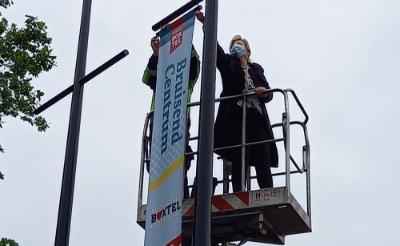 <p>Wethouder Mari&euml;lle van Alphen bevestigt de eerste banier aan de mast. Bruisend Centrum Boxtel is nu nog zichtbaarder. (Foto: Jan Hermens)</p>