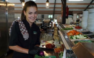 <p>Fenna Maas snijdt uien, komkommers en tomaten in de keuken van speelboerderij Gouden Woud. De Liempdse heeft het prima naar haar zin op haar werk. (Foto: Gerard Schalkx).</p>