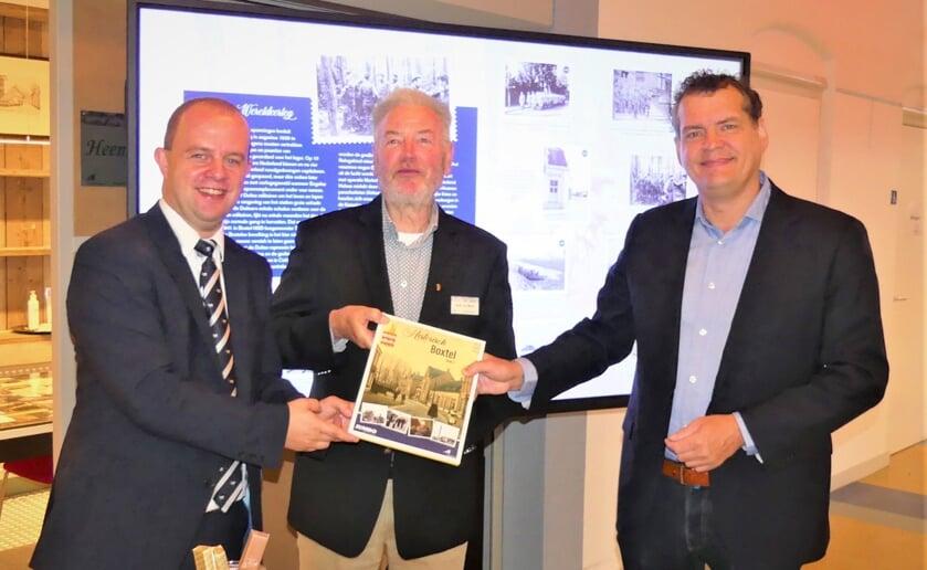 <p>Filiaalmanager Oskar Martens van Jumbo Oosterhof (links) en Henk van Beers van Heemkunde Boxtel (midden) geven het eerste exemplaar aan wethouder Hans Heesen van de gemeente Boxtel. (Foto: Ad van de Wetering).</p>