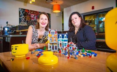 Legomaster Lola Nouwens (links) en jongerenwerker Sháron Willems slaan de handen ineen. Het duo gaat 24 jongeren begeleiden terwijl die hun fantasie met de bouwsteentjes de vrije loop laten. (Foto: Bas van den Biggelaar).