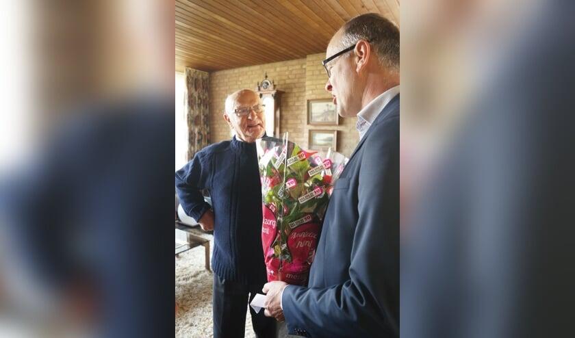 De heer Van Toor is verrast dat wethouder Geert Hendriks hem een bloemetje komt brengen.
