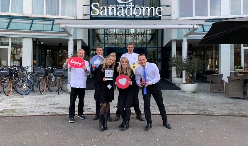 Trotse team members van Sanadome poseren met de award voor de ingang van het wellnesshotel.